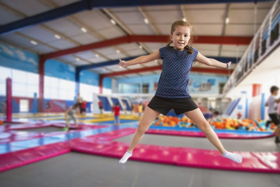 Trampoline Park Insurance - Cheerful Young Girl With Pigtails and Smiling While Jumping on a Trampoline