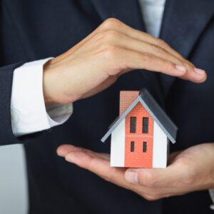 An image of a man in a suit holding a small model of a house