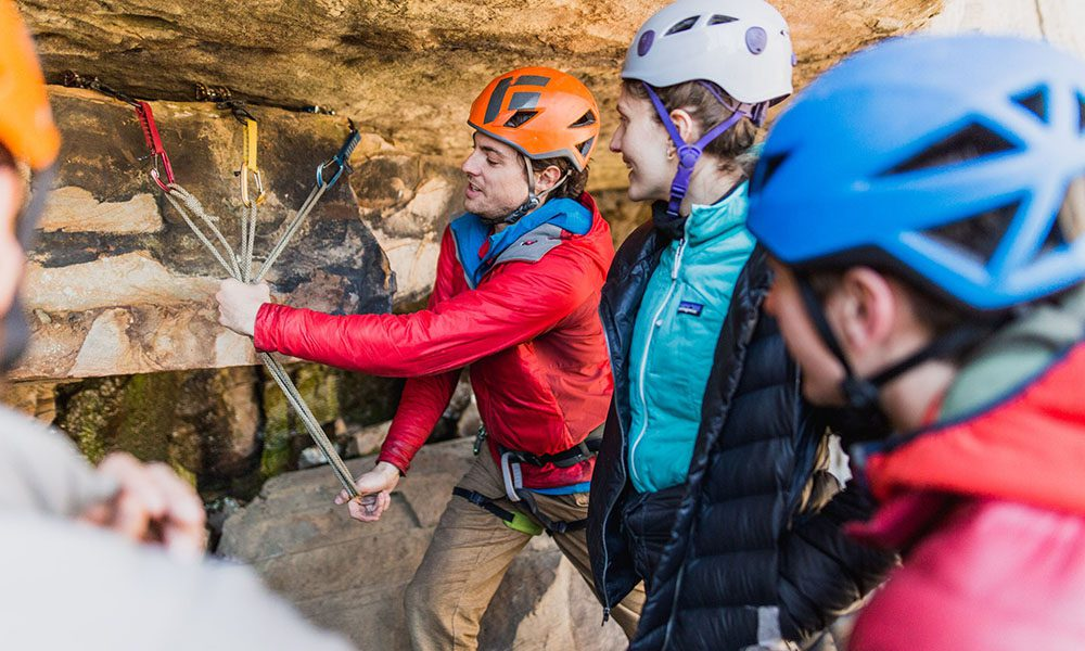 Blog - Gym to Crag Risk Management with Granite Insurance - Climbing Instructor Demonstrating Climbing Tips With A Class