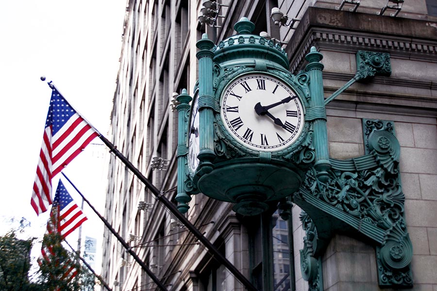 About Our Agency - Old Green Ornate Metal Clock Mounted on the Corner of a Stone Building in Chicago, With Flagpoles Attached to the Building Waving American Flags