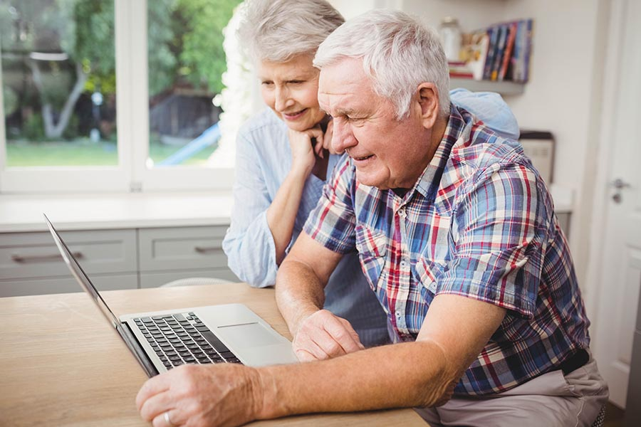 Blog - Senior Couple Read a Laptop Together in Their Sunny Kitchen at the Kitchen Table