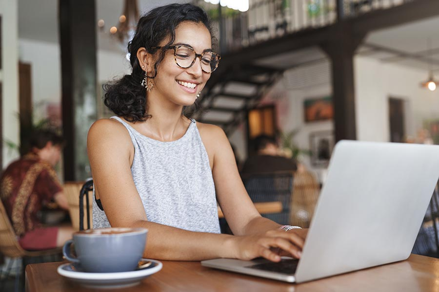 Client Center - Young Woman in a Bustling Cafe Smiles and Uses Her Laptop With a Cappuccino Beside Her
