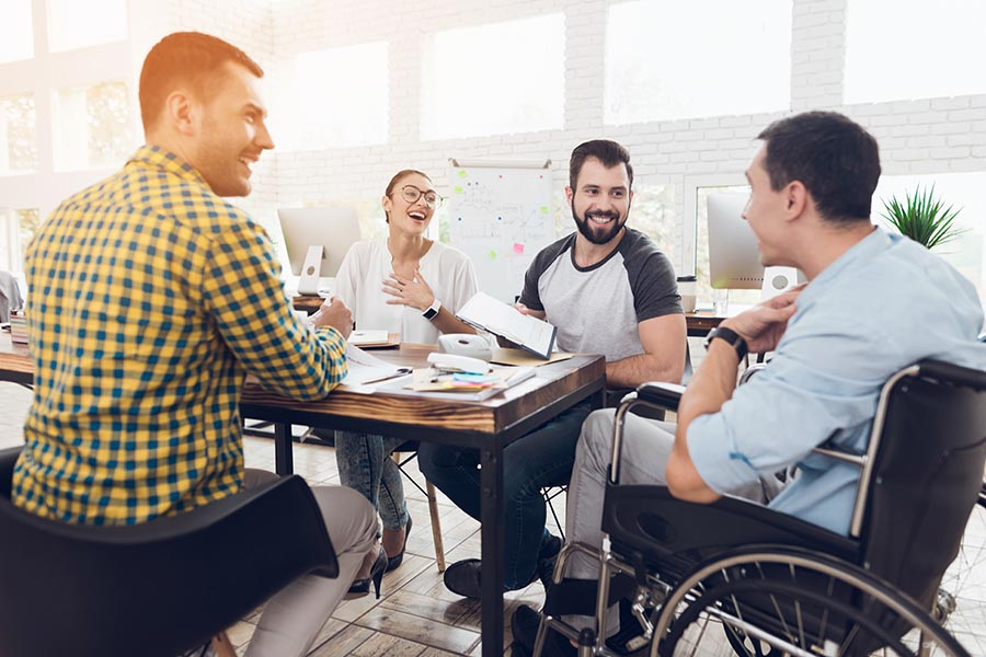 Employee Benefits - Group of Coworkers Sit at a Conference Table Laughing and Collaborating on Their Work