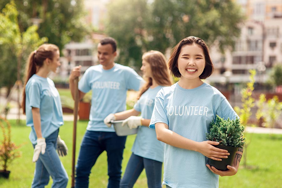 Specialized Business Insurance - Young Woman Holding a Potted Shrub and Wearing a Volunteer Shirt Smiles While Fellow Volunteers Chat Behind Her