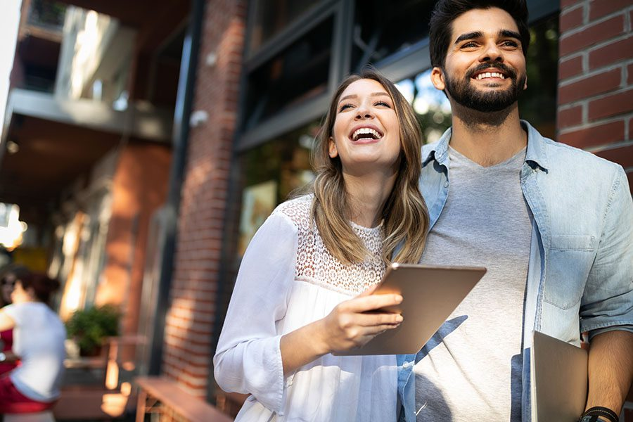 Client Center - Joyful Young Couple Standing Next to a Restaurant in the City While Using a Tablet