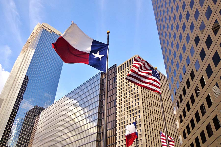 Contact - View of Texas and American Flags in Front of Modern Commercial Buildings in Houston Texas