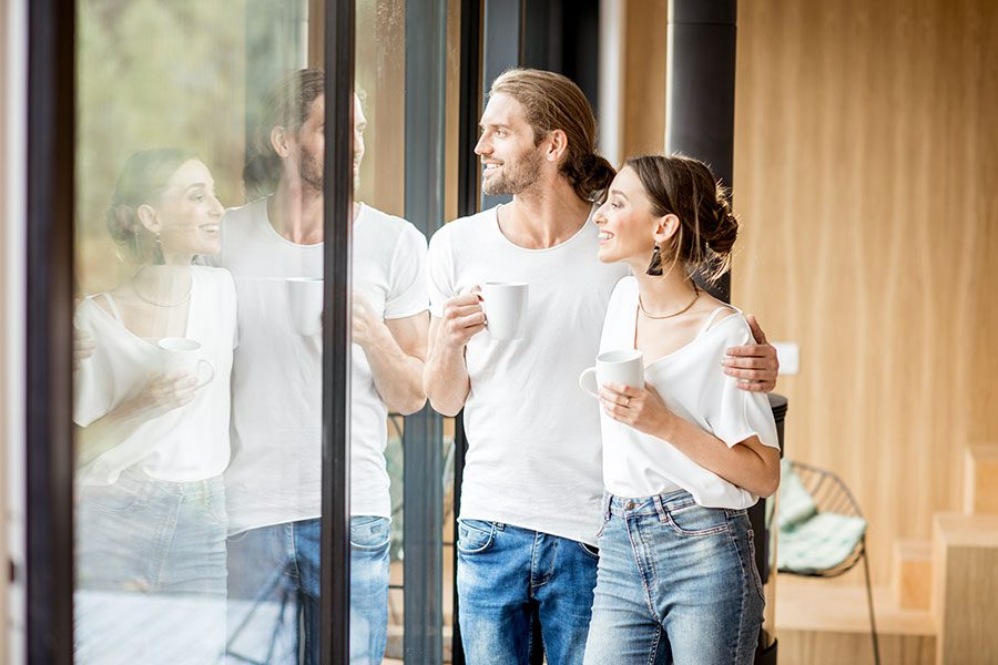 Insurance Quote - Young Couple Drinking Coffee and Looking Outside from the Glass Doors Inside Their Modern Home
