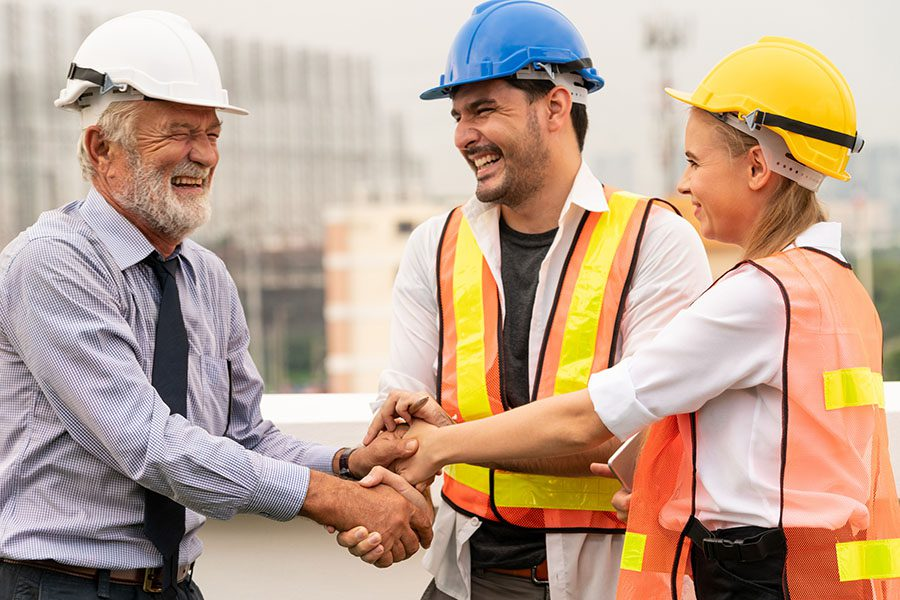 Specialized Business Insurance - Engineer and Two Smiling Contractors Standing on a Construction Jobsite Shaking Hands to Celebrate Success