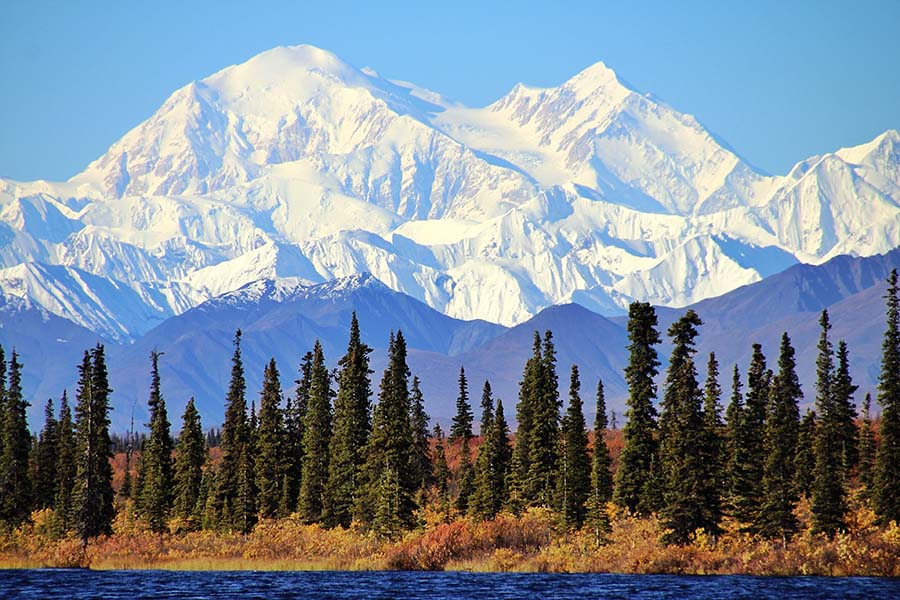 Alaska Cannabis Insurance - View of Glaciers on Mountain Top and Surrounding Forests and Lake in Alaska