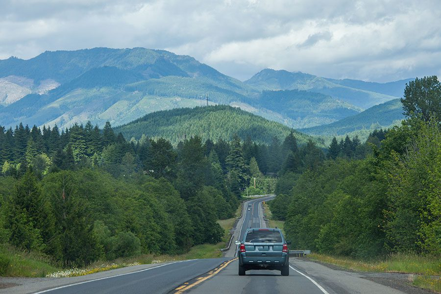 Auto Insurance in Washington - Car Driving on the Highway with Views of the Forest and Mountains