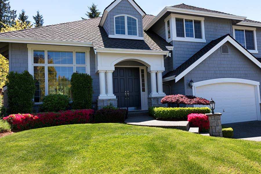 Home Insurance in Washington - Exterior of a Modern Two Story Home with an Attached Garage and Green Landscaped Front Yard