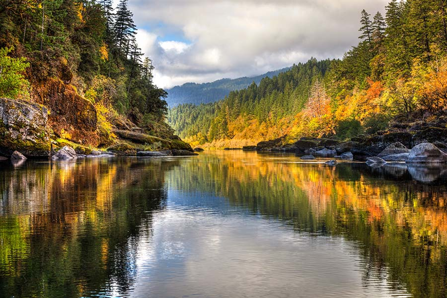 Oregon Cannabis Insurance - View of Colorful Fall Foliage Reflected on the River with Views of the Mountains in the Background in Oregon