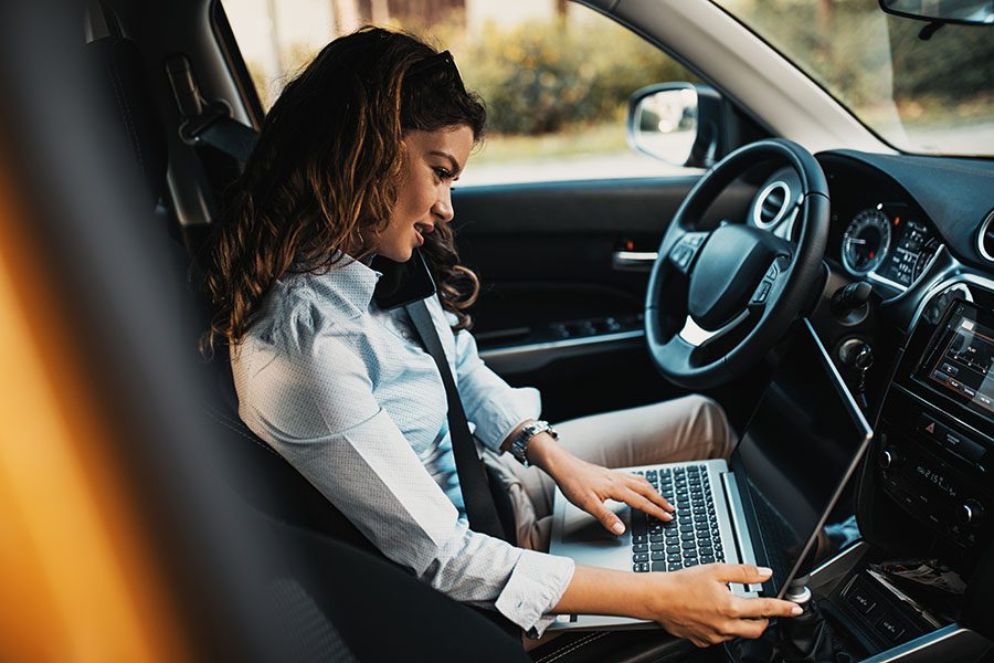 Target Zero Distracted Driving Initiative - View of a Woman Sitting in Her Car While Using a Laptop and Her Cellphone