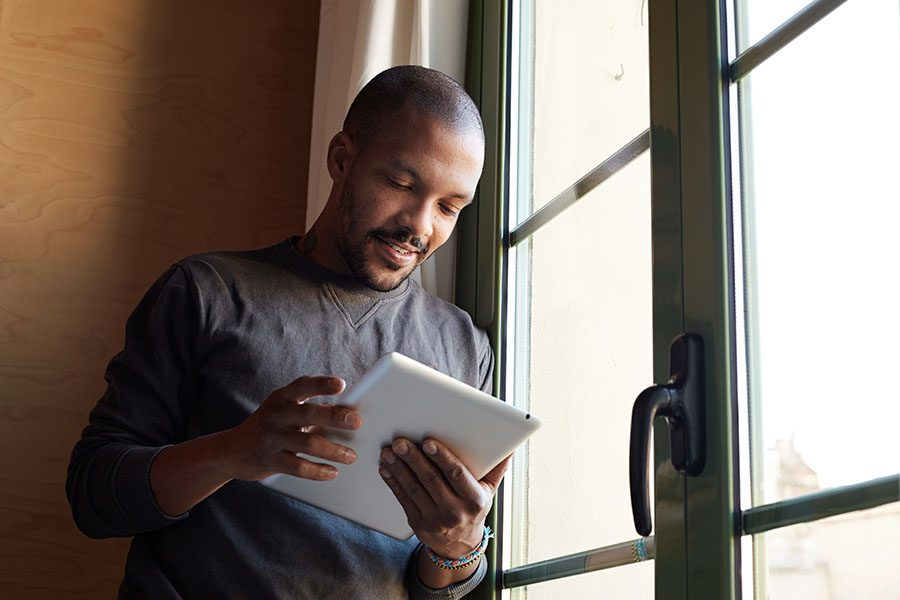 Video Library - Portrait of a Man Standing Next to a Glass Door at Home Using a Tablet