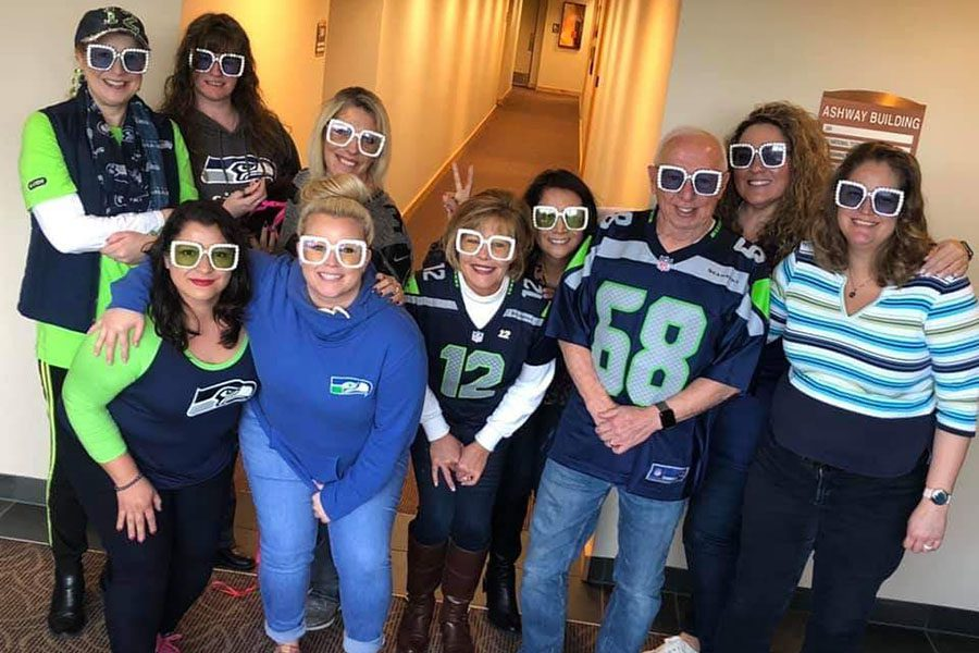 About Our Agency - Photo of Mosaic Insurance Team Posing in the Office Wearing Sports Jerseys and Funny Glasses