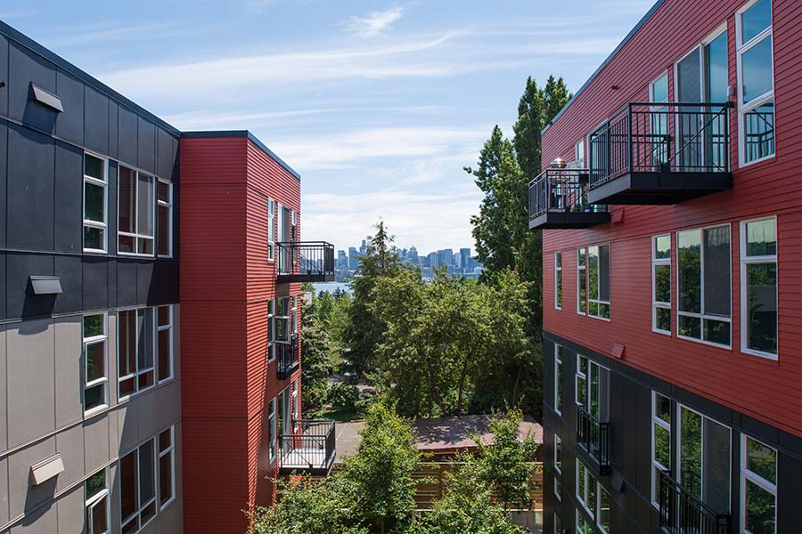 Specialized Business Insurance - Red and Black Apartment Buildings with a View of Downtown Seattle Washington Skyline in the Background