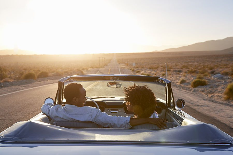 Auto Insurance Renewal - Rear View of a Couple Driving in a Convertible Towards the Sunset
