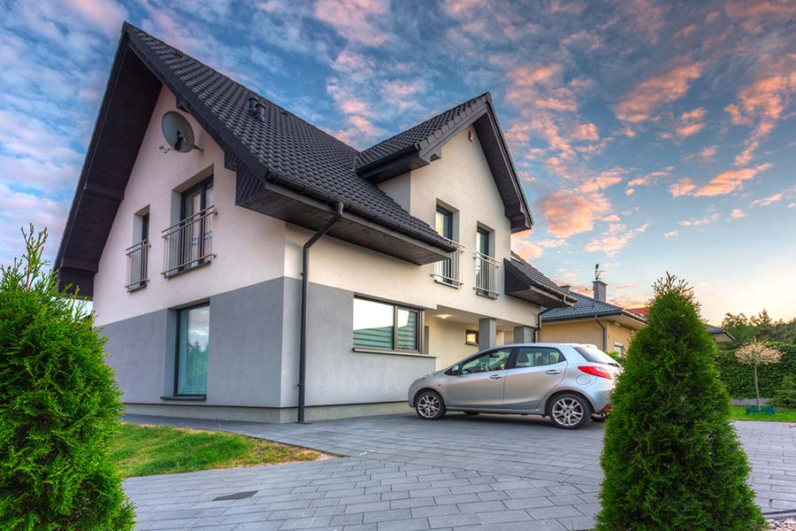 Auto and Home Insurance Report Card - View of a Modern Two Story Home with a Car Parked in Front of the House Against a Colorful Sky