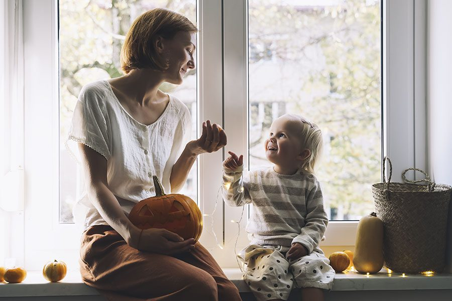 Home Insurance Renewal - View of Happy Mother and Daughter Sitting Next to the Window in Their Home Getting Ready to Carve a Pumpkin for Halloween