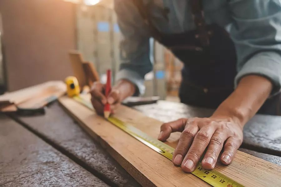 Carpenter-Insurance-Carpenter-Working-With-Equipment-on-Wooden-Table-in-Workshop