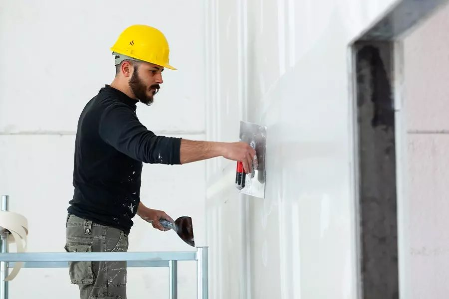 Drywall-Contractor-Insurance-Drywall-Worker-in-Yellow-Helmet-Plastering-Wall-While-Standing-on-Scaffold