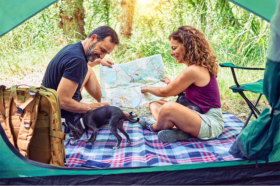 Personal Long Term Care Insurance - Man and Woman Camping Together and Looking At A Map Together With Their Small Dog
