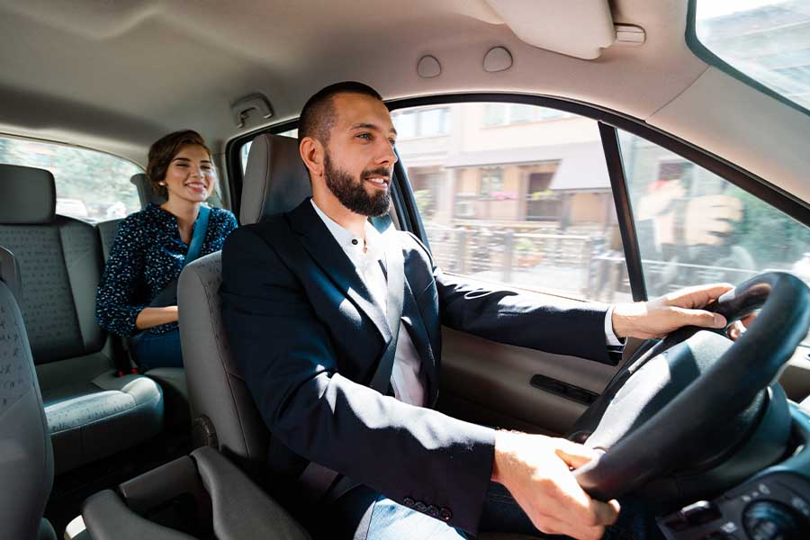 Livery-Insurance-Smiling-Livery-Driver-Sitting-in-a-Car-with-a-Young-Businesswoman-While-Driving-to-Her-Next-Destination-in-a-Busy-City