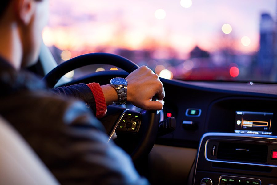 SR-22-Closeup-View-of-a-Man-Driving-His-Vehicle-with-Outside-of-Car-Out-of-Focus-at-Dusk