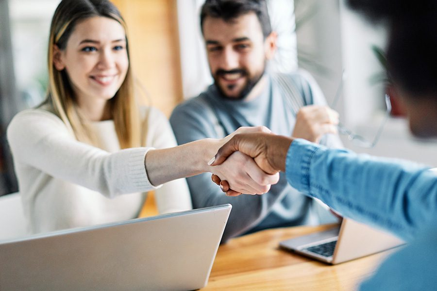 Tax Season FAQs - Couple Sitting Down in the Office with Insurance Agent and Woman is Shaking Hands with the Agent
