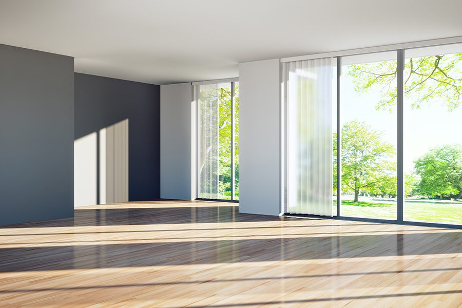 Vacant Home Insurance - Inside of a Bright Modern Vacant Home with Dark Walls and Sliding Glass Doors Leading to a Green Landscaped Yard with Trees on a Sunny Day