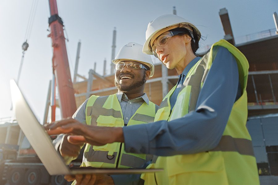 Business Insurance - View of Smiling Contractor and Engineer Standing at a Construction Jobsite and Looking at Building Plans on a Laptop