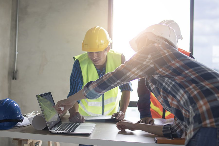 Client Center - Group of Contractors Having a Meeting in a Building Looking at Building Plans on a Laptop