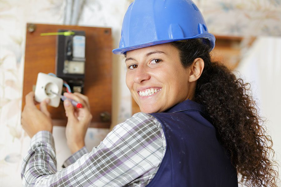 Contact - Closeup View of Smiling Female Electrician Working on Fixing an Electrical Socket Problem
