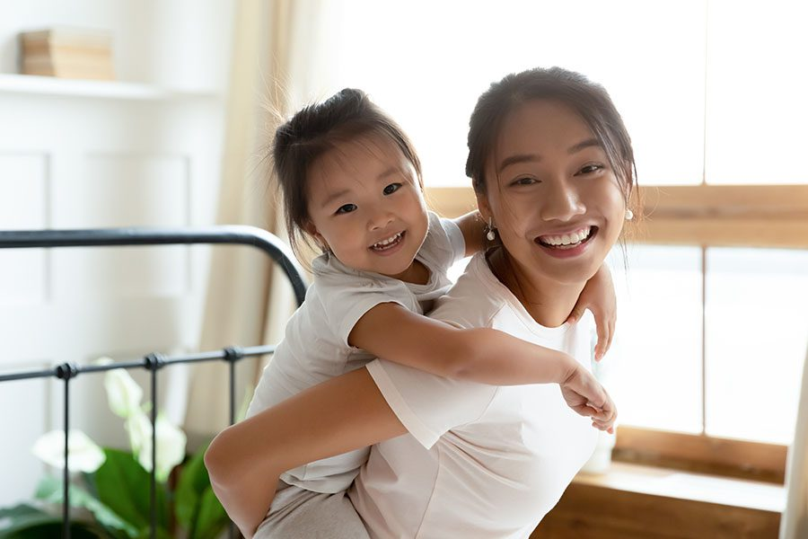 Personal Insurance - View of Smiling Mother Giving Her Happy Daughter a Piggyback Ride at Home
