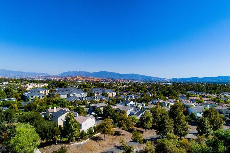 Santa Clarita CA - Aerial View of the Suburbs of Santa Clarita California with Views of Residential Homes Surrounded by Green Trees