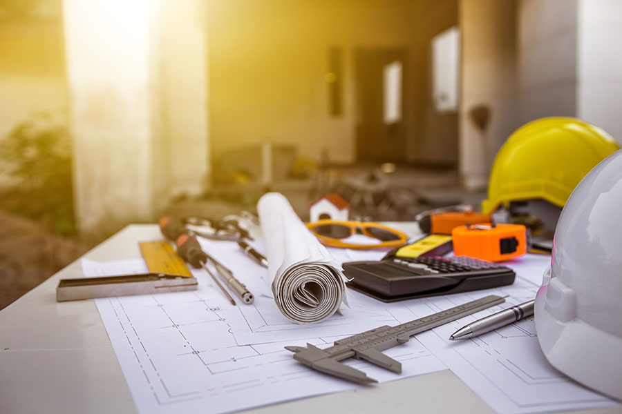 Specialized Business Insurance - Closeup View of Table Inside a Newly Constructed Building with Various Contractor Tools and Building Blueprints