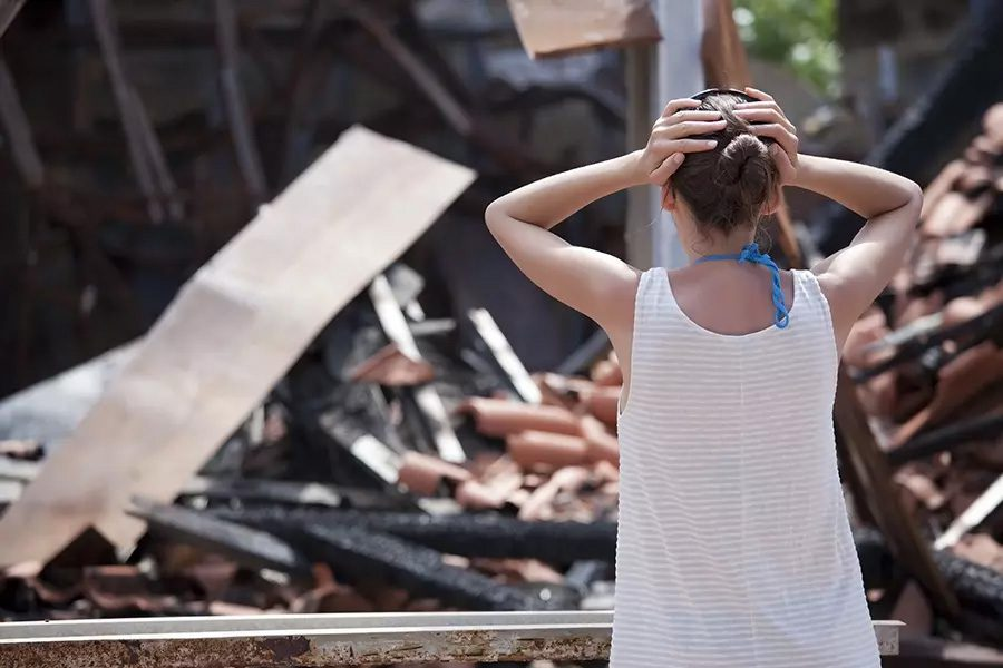 Difference-in-Conditions-Insurance-Woman-with-Arms-Raised-Stands-in-front-of-Her-Storm-Damaged-Home