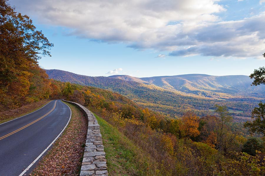 About Our Agency - a Winding Road Hugs the Edge of a Mountain Overlooking the Shenandoah Valley in Virginia, White Clouds Overhead and the Sun Shining on the Valley