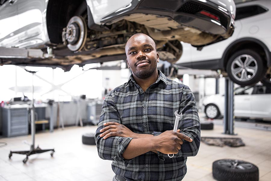 Business Insurance - an Auto Repair Garage Owner Stands Holding Tools, a Car Lifted Above Him