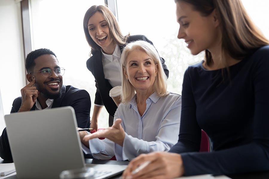 Employee Benefits - Group of Employees Laugh and Collaborate Over a Laptop at Work