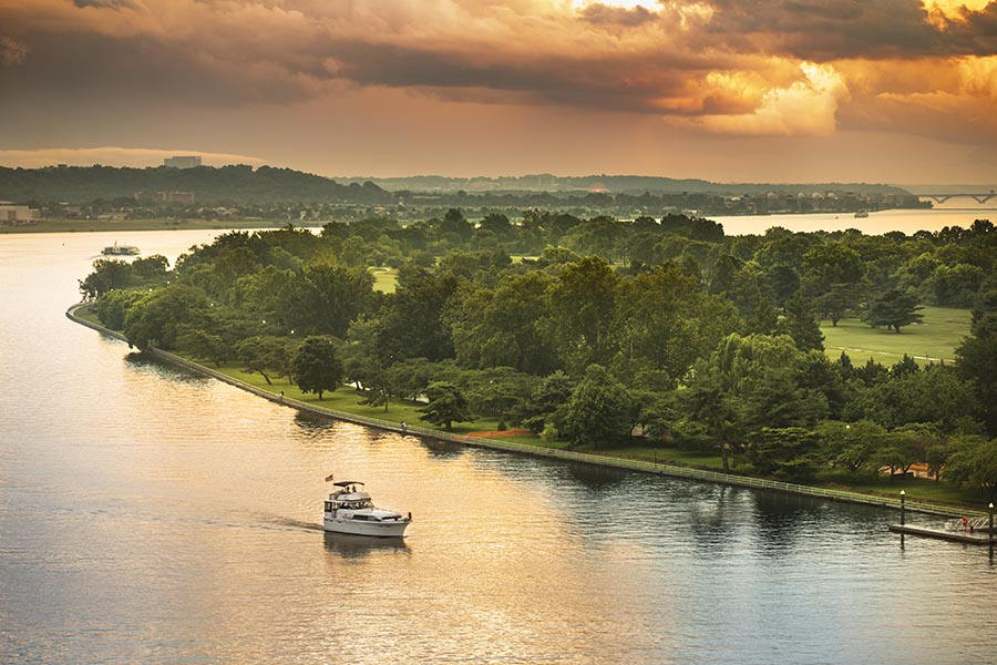Leesburg, VA Insurance - a Boat Moves Slowly Along the Potomac River at Sunset, Green Trees Lining the Shore, Orange Clouds Overhead