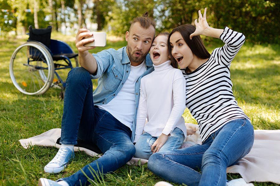 Personal Insurance - a Father, Daughter and Mother Take a Funny Selfie Photo, Sitting on a Picnic Blanket in a Park, a Wheelchair Sitting Behind Them