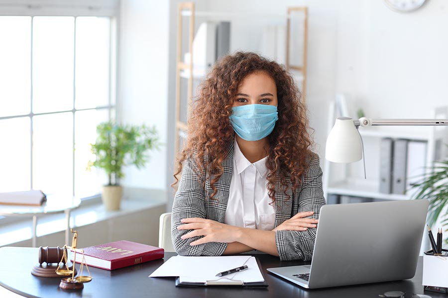 COVID-19 Information - Businesswoman at a Desk With Computer Wearing a Mask in Modern Office