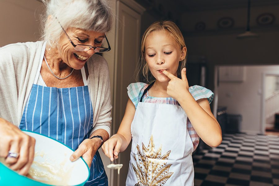 About Our Agency - View of Smiling Grandmother and Granddaughter Standing in the Kitchen Baking Together