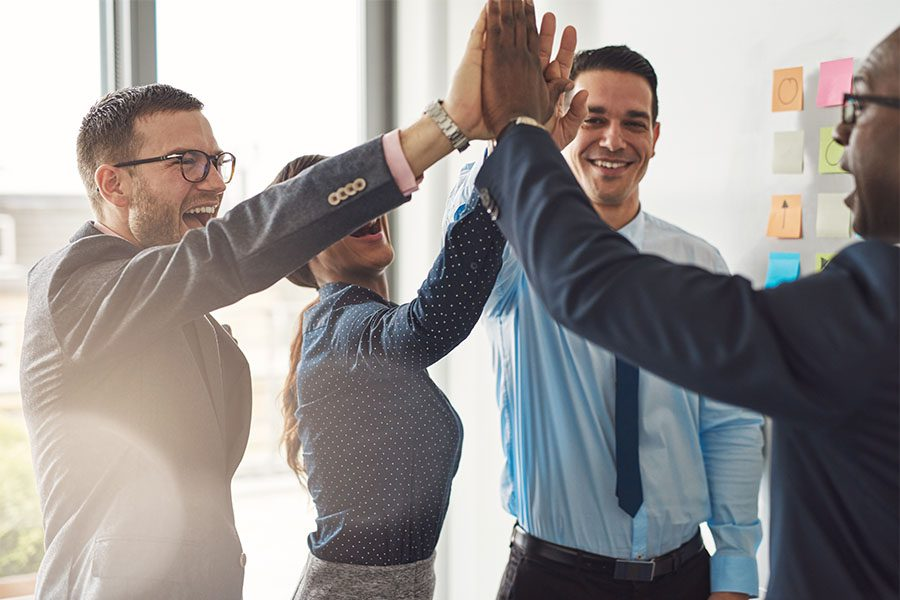 Business Insurance - Group of Colleagues at a Business Meeting in the Office Giving Each Other High Fives to Celebrate Success