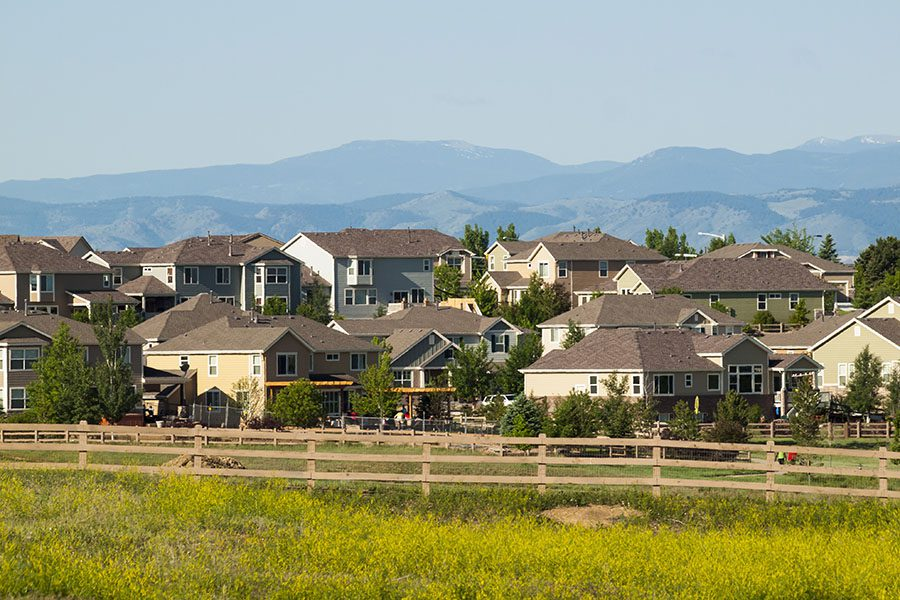 Centennial CO - View of Luxury Homes Surrounded by Wooden Fence in Centennial Colorado with Views of Mountains in the Background