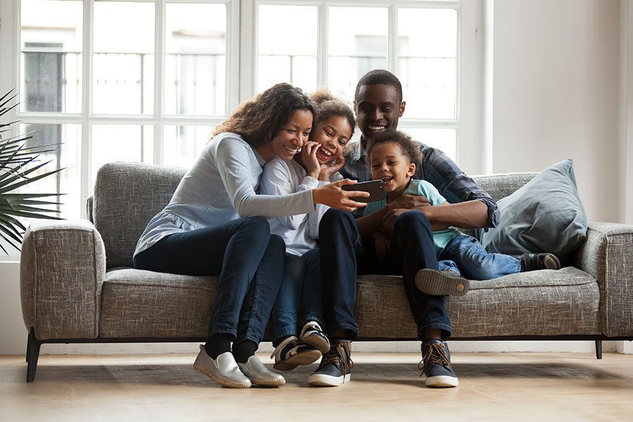 Client Center - Portrait of a Cheerful Family with Two Kids Sitting in the Living Room Having Fun Watching Videos on a Phone