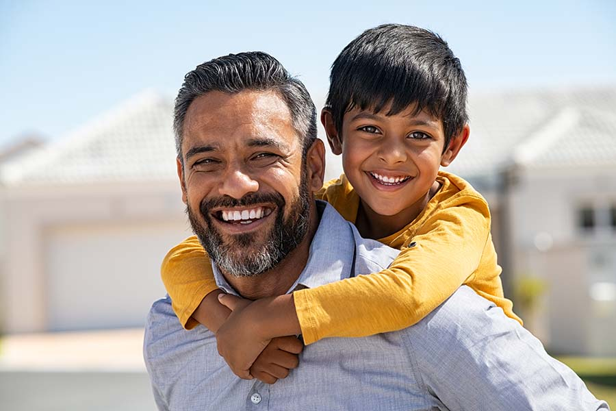 Insurance Quote - Closeup View of Smiling Father Giving His Son a Piggyback Ride Outside in Front of Their House