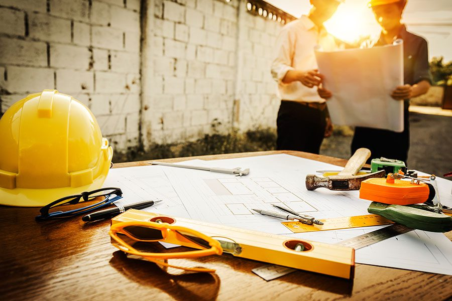 Specialized Business Insurance - Closeup View of Wooden Table With Blueprints and Construction Tools with View of Two Contractors Standing in the Background