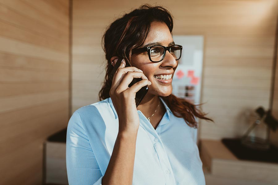 Contact Us - Businesswoman in Black Glasses Looks Towards a Window as She Smiles and Makes a Phone Call